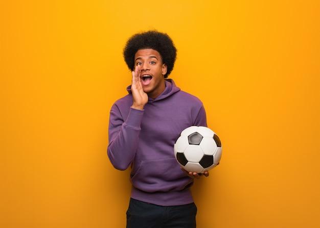 Jovem americano africano esporte homem segurando uma bola de futebol gritando algo feliz para a frente Foto Premium