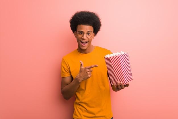 Jovem, americano africano, segurando, um, pipoca, balde, apontar, ao lado, com, dedo Foto Premium