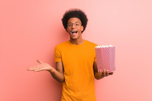Jovem, americano africano, segurando, um, pipoca, balde, celebrando, um, vitória, ou, sucesso Foto Premium