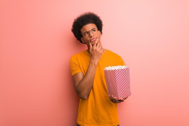 Jovem, americano africano, segurando, um, pipoca, balde, duvidar, e, confundido Foto Premium