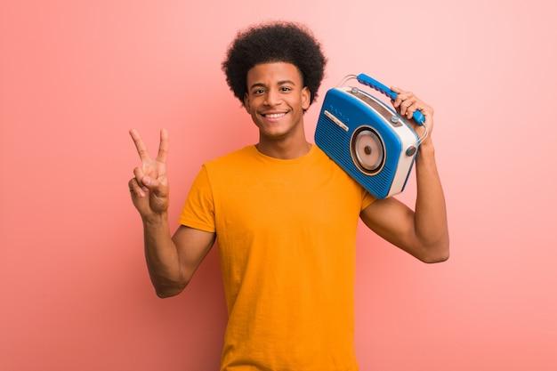 Jovem, americano africano, segurando, um, rádio vintage, mostrando, numere dois Foto Premium