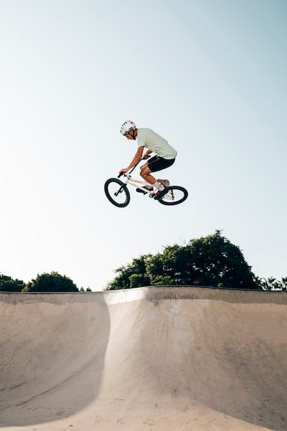 Jovem andando de bicicleta bmx em uma rampa Foto gratuita