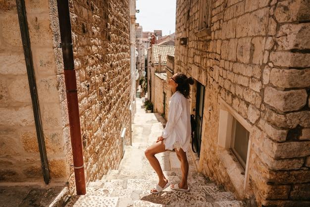 Jovem andando pelas ruas estreitas antigas em um lindo dia de verão Foto gratuita