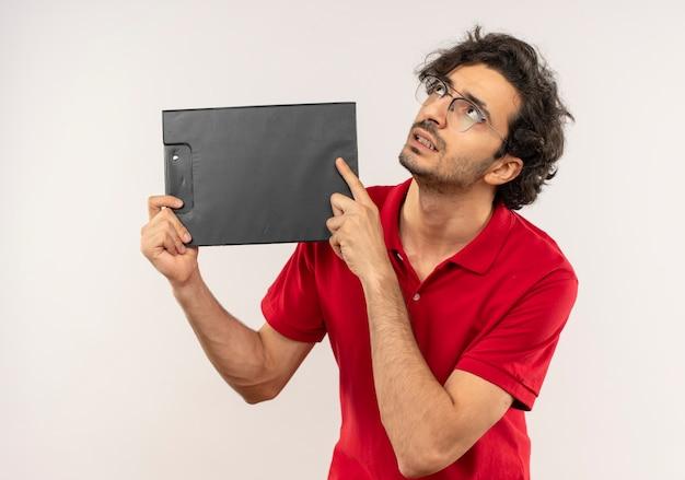 Jovem ansioso de camisa vermelha com óculos ópticos segurando uma prancheta e olhando para cima, isolado na parede branca Foto gratuita