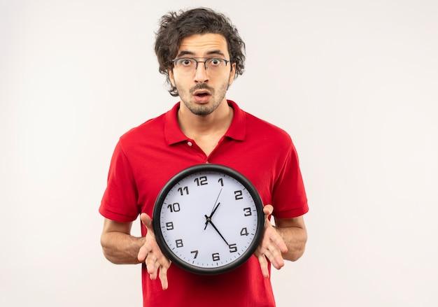 Jovem ansioso de camisa vermelha com óculos óticos segurando relógio e parece isolado na parede branca Foto gratuita
