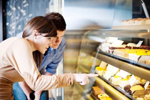 Jovem apontando para bolos em confeitaria Foto gratuita