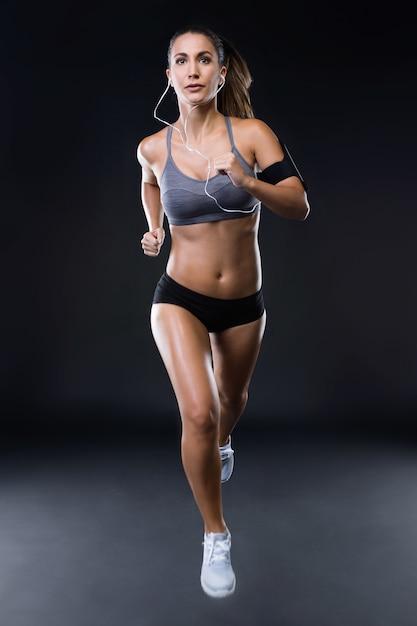 Jovem apta e desportiva que corre sobre o fundo preto. Foto gratuita