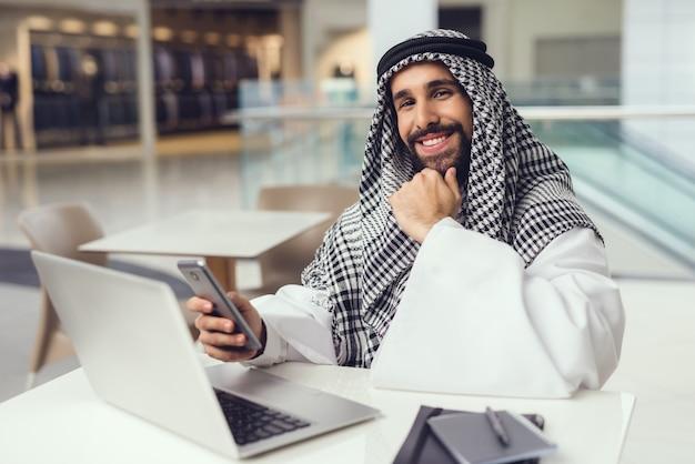 Jovem, árabe, homem, usando, telefone, e, laptop, em, café Foto Premium