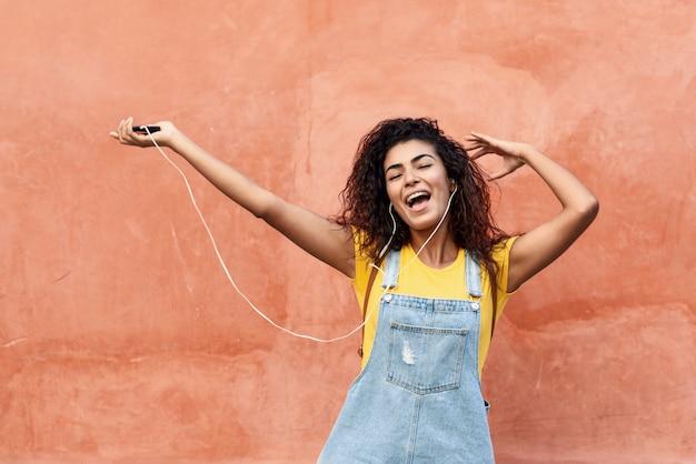 Jovem, árabe, mulher, escutar música, com, fones ouvido, ao ar livre Foto Premium
