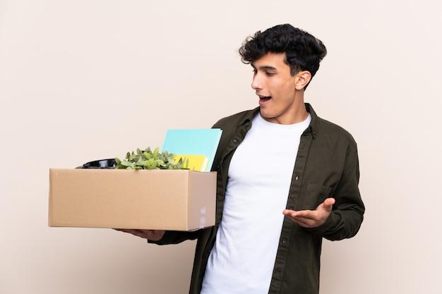 Jovem argentino, movendo-se em nova casa sobre parede isolada com expressão facial de surpresa Foto Premium