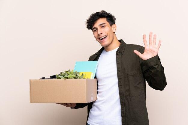 Jovem argentino, movendo-se em nova casa sobre parede isolada, saudando com mão com expressão feliz Foto Premium