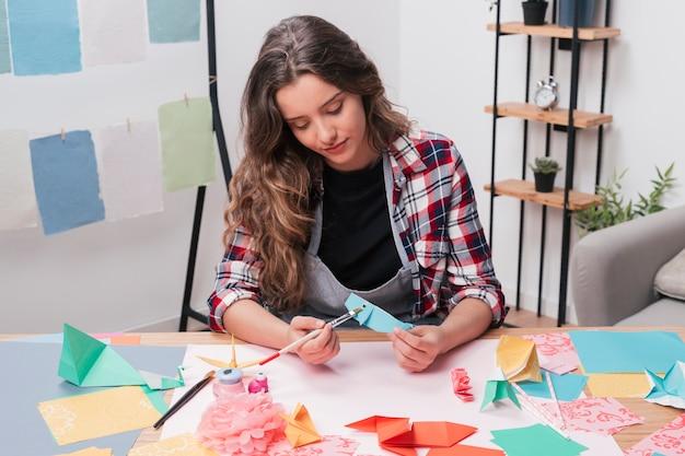 Jovem, artista bonito, mulher, quadro, origami, peixe, usando, pincel Foto gratuita