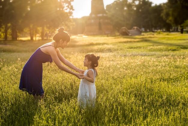 Jovem, ásia, mãe, tendo divertimento, com, filha, em, campo, com, luz solar, ligado, capim Foto Premium