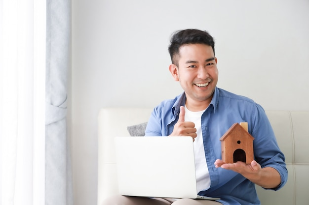 Jovem, asian tripulam, em, camisa azul, com, computador laptop, e, pequeno, casa, modelo, mostrando, para, empréstimo banco, para, casa, conceito, em, sala de estar Foto Premium