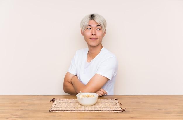 Jovem asiática com ramen em uma mesa rindo Foto Premium