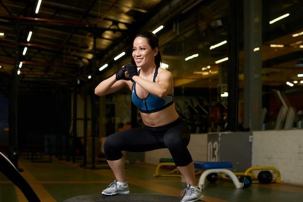 Jovem asiática em boa forma física fazendo agachamentos em uma academia Foto gratuita