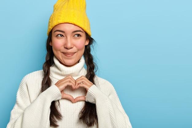 Jovem asiática encantadora e satisfeita faz sinal de coração, confessa namorado apaixonado, tem expressão facial satisfeita, olha para o lado, usa chapéu amarelo e macacão Foto gratuita