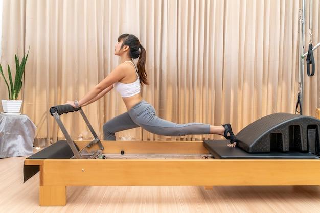Jovem asiática trabalhando em uma máquina reformadora de pilates durante seu treinamento de exercícios de saúde para esticar as pernas Foto Premium