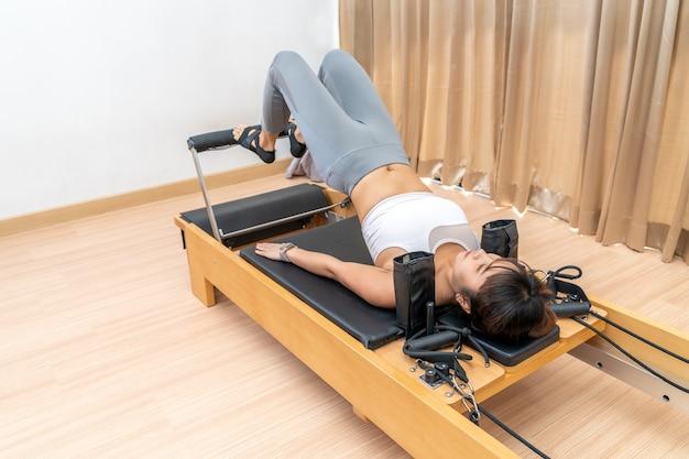 Jovem asiática trabalhando em uma máquina reformadora de pilates durante seu treinamento de exercícios de saúde Foto Premium