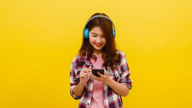 Jovem asiática usando fones de ouvido sem fio, ouvindo música de smartphone com expressão alegre em roupas casuais e olhando para a câmera sobre parede amarela. conceito de expressão facial. Foto gratuita