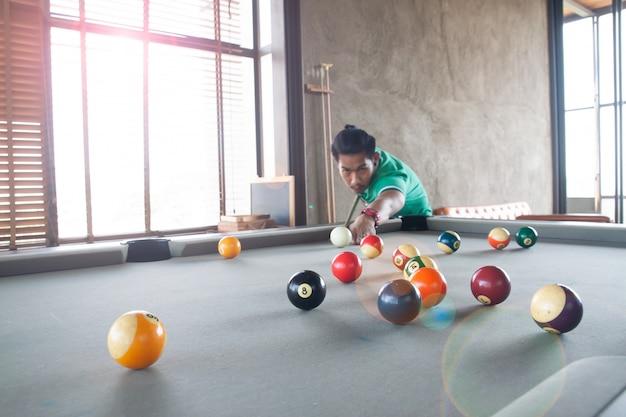 Jovem asiático bonito que joga a associação em casa, foco seletivo na bola Foto Premium