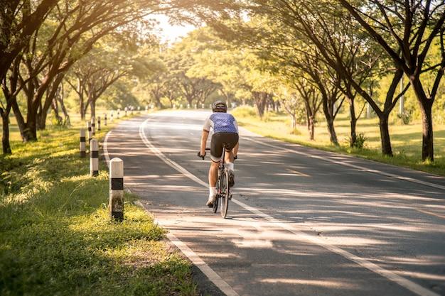 Jovem, asiático, ciclista, montando, um, bicicleta, ligado, um, estrada aberta, para, a, pôr do sol Foto Premium