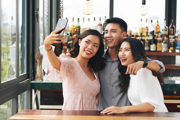 Jovem asiático e duas mulheres abraçando e tomando selfie no smartphone em bar Foto gratuita