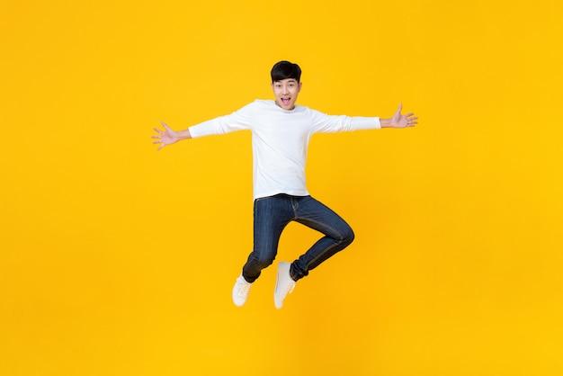 Jovem asiático em roupas casuais pulando Foto Premium