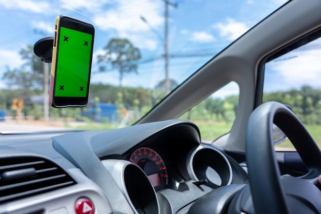 Jovem asiático homem motorista um carro na cidade e smartphone com tela verde em branco Foto Premium