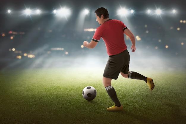 Jovem, asiático, jogador futebol, com, a, bola Foto Premium