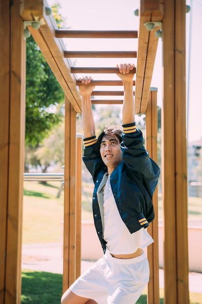 Jovem asiático malhando na selva gym Foto gratuita