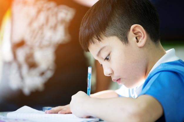 Jovem, asiático, menino, fazendo, seu, dever casa Foto Premium
