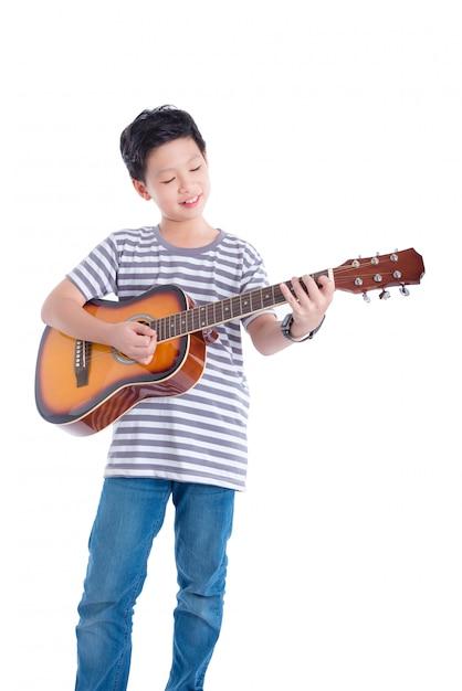 Jovem, asiático, menino, violão jogo, e, sorrisos, sobre, fundo branco Foto Premium