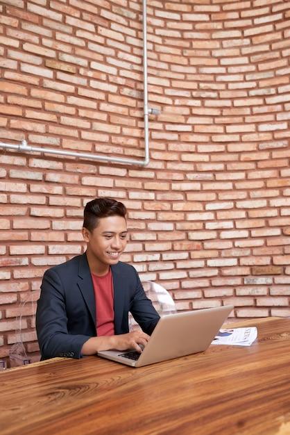 Jovem asiático sentado à mesa de madeira e trabalhando no laptop e parede de tijolo no fundo Foto gratuita