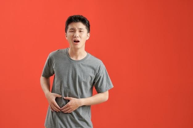 Jovem asiático vestindo uma camiseta branca doente, com dor de estômago Foto Premium