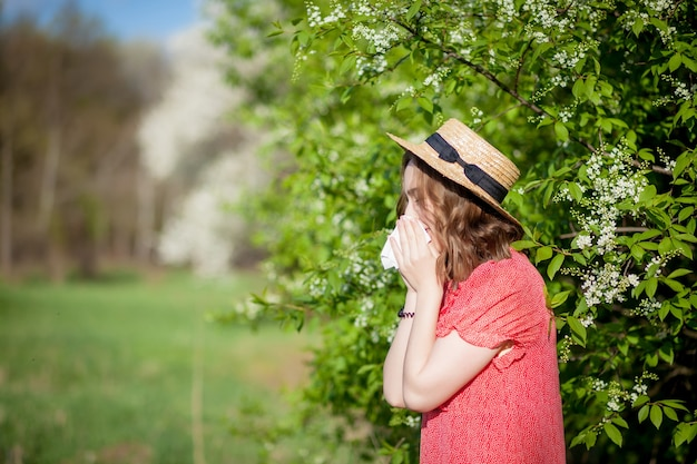 Jovem assoando o nariz e espirrando em um lenço de papel na frente de uma árvore florescendo. alergênicos sazonais que afetam as pessoas. bela dama tem rinite. Foto Premium