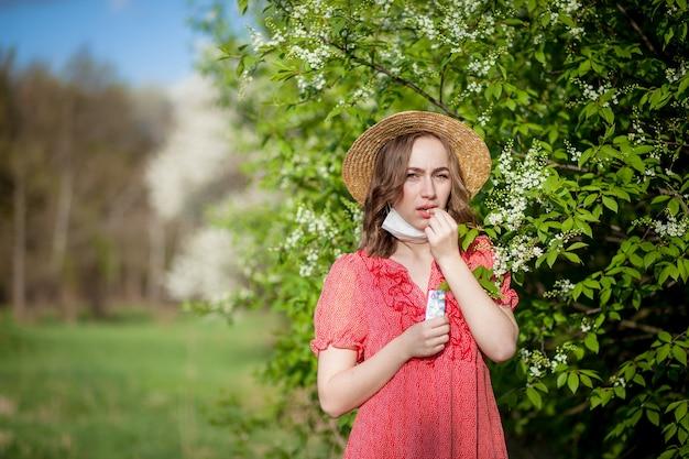 Jovem assoando o nariz e espirrando no lenço na frente de uma árvore florescendo. alergênicos sazonais que afetam as pessoas. bela dama tem rinite. Foto Premium