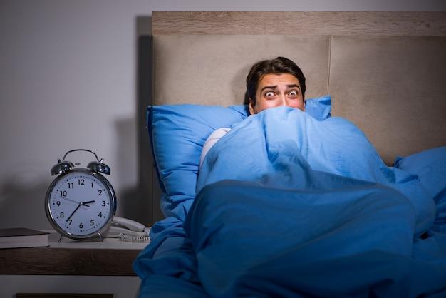 Jovem assustado na cama Foto Premium