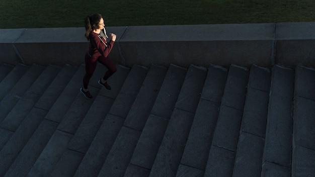 Jovem ativa subir escadas Foto gratuita