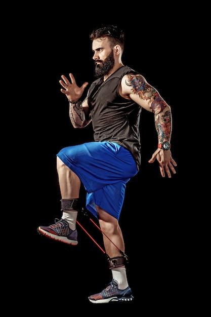 Jovem atleta de cócoras exercício com banda de resistência ao redor das pernas. comprimento de corpo inteiro sobre fundo preto studio. Foto Premium