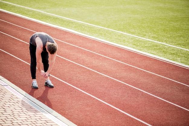 Jovem atleta do sexo masculino em pé na pista de corrida, esticando as mãos Foto gratuita
