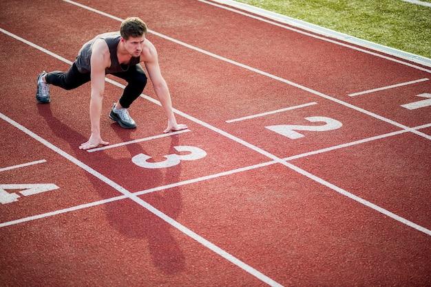 Jovem atleta na posição inicial, pronta para começar uma corrida Foto gratuita