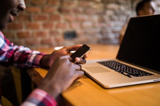 Jovem atraente empresário afro-americano com óculos e laptop sentado no café bar e usar o telefone celular. Foto gratuita