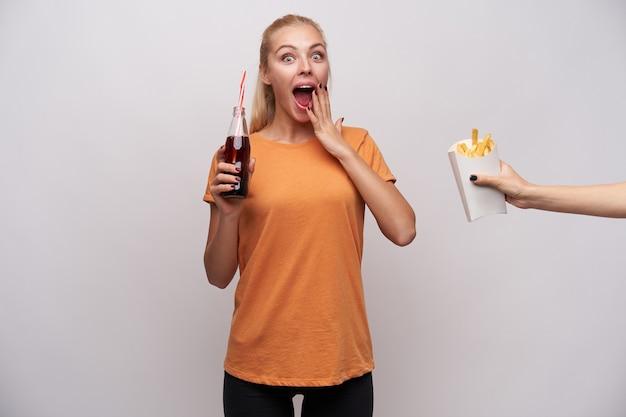 Jovem atraente loira de olhos azuis surpresa olhando para a câmera com os olhos arregalados e a boca aberta, segurando a garrafa de refrigerante e animada com alguém tratando de suas batatas fritas Foto gratuita