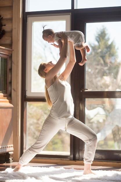 Jovem atraente mãe desportiva fazendo exercícios com seu bebê Foto gratuita