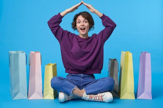 Jovem atraente morena com cabelo curto e muitas sacolas de compras Foto gratuita