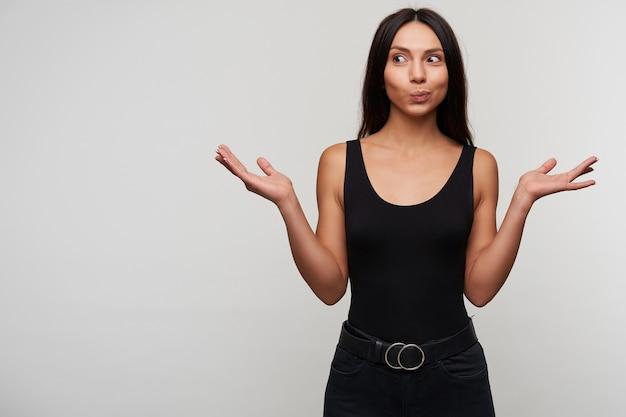 Jovem atraente morena de cabelos compridos surpresa feminina olhos arredondados enquanto olha positivamente para o lado e levantando as palmas das mãos, vestida com roupas pretas casuais enquanto posa Foto gratuita