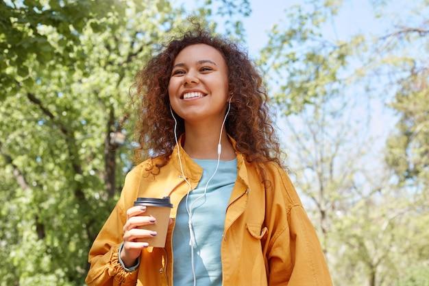 Jovem atraente, morena, encaracolada, sorrindo, vestindo uma jaqueta amarela, segurando uma xícara de café, caminhando no parque, ouvindo música e curtindo o clima. Foto gratuita