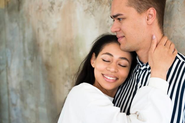 Jovem, atraente, mulher, abraçar, namorado, contra, concreto, parede Foto gratuita