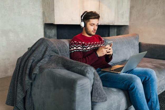 Jovem atraente no sofá em casa no inverno com smartphone em fones de ouvido, ouvindo música, vestindo uma camisola de malha vermelha, trabalhando no laptop, freelancer Foto gratuita